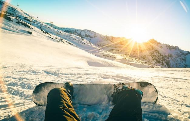 Snowboarder zit bij zonsondergang op een ontspannen moment in het skigebied van de franse alpen