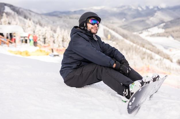 Snowboarder zittend op een skihelling voor rit
