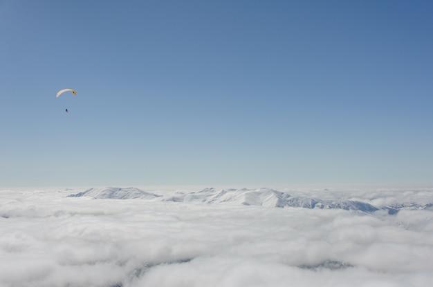 Snowboarders vliegen op een paraglider boven de wolken