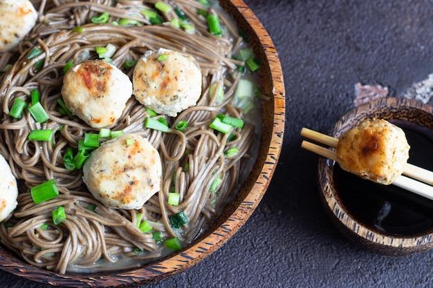 Soba-noedels geserveerd met kippenvleesballetjes en groene ui.