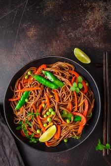 Soba-noedels van het veganistboekweit met groenten in zwarte plaat, hoogste mening.