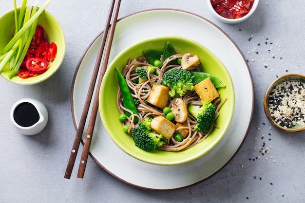 Sobanoedels met groenten en gebraden tofu in een kom. bovenaanzicht detailopname.