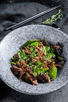 Sobanoedels met rundvlees, wortelen, uien en paprika. roerbak de wok. zwarte achtergrond. bovenaanzicht