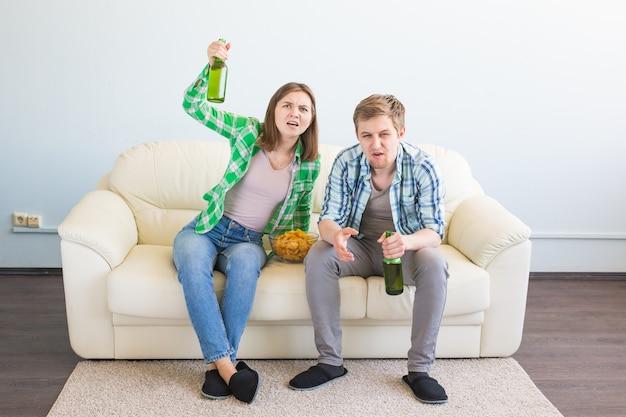 Soccer world cup concept - paar vrienden zitten in de bank kijken naar sportwedstrijd op tv