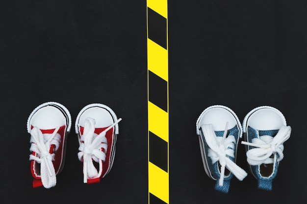 Sociaal afstandsconcept. sneakers op een achtergrond van asfalt. ruimte kopiëren. houd afstand om de verspreiding van het virus te voorkomen. nieuwe realiteit tijdens de coronavirusepidemie.