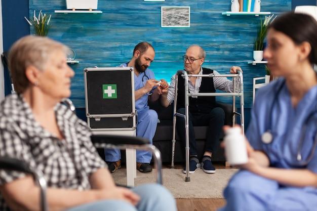Sociaal assistent die medicijnen voor de gezondheidszorg bespreekt met bejaarde gehandicapte gepensioneerde