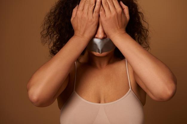 Sociaal concept om agressie en geweld tegen vrouwen te helpen bestrijden en elimineren. bange vrouw met verzegelde mond die haar ogen bedekt met handen, geïsoleerd op een donkere beige achtergrond met kopieerruimte