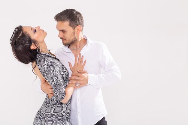 Sociaal dansconcept - actieve gelukkige volwassenen die samen bachata of salsa dansen over witte muur met exemplaarruimte