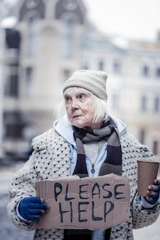 Sociaal probleem. depressieve oudere vrouw die op straat bedelt zonder geld te hebben om te leven