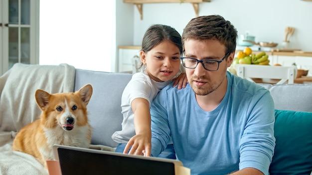 Social distancing. een drukke vader probeert thuis met zijn kind en vrouw op afstand te werken. de dochter bemoeit zich met het werk van de vader. op de achtergrond is de vrouw bezig in de keuken.