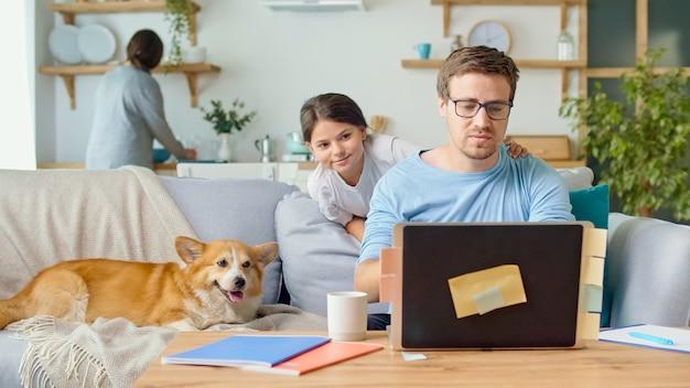 Social distancing. een drukke vader probeert thuis op afstand te werken met zijn kind en vrouw.