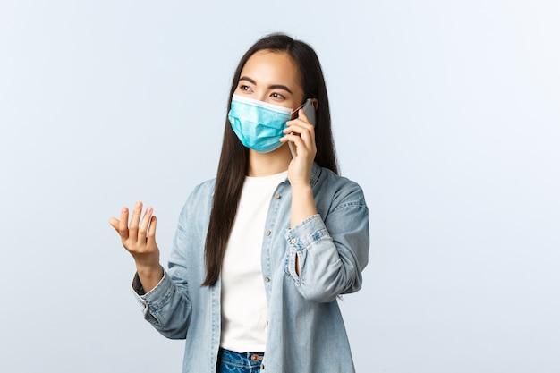 Social distancing lifestyle, covid-19 pandemie en mensen emoties concept. zorgeloos aziatisch meisje met medisch masker dat aan de telefoon praat, een mobiel gesprek voert en gebaren maakt.