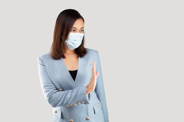 Social distancing. zakenvrouw zeggen stop ontkenning gebaar. voeg grijze ruimte aan de rechterkant toe. vrouw toont haar ontkenning zonder nee op haar hand