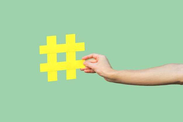 Social media concept, close-up portret van hand met grote grote gele hash tag teken. binnen, geïsoleerd, kopieer ruimte, groene achtergrond, marketing symbool, instagram volgers
