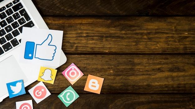 Social media iconen met zoals pictogram op laptop over houten achtergrond