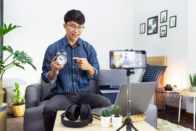 Social media influencer of blogger presenteren en beoordelen opname of streaming vlog over product met smartphone op statief voor sociale mediakanaal waardoor livestream-concept wordt gemaakt.