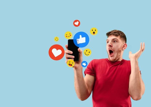 Social media-interacties op mobiele telefoon. digitale internetmarketing, chatten, reageren, leuk vinden. glimlach en pictogrammen boven het smartphonescherm, dat door een jonge man op een blauwe studioachtergrond wordt vastgehouden.
