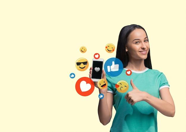 Social media-interacties op mobiele telefoon. digitale internetmarketing, chatten, reageren, leuk vinden. glimlach en pictogrammen boven het smartphonescherm, dat door een jonge vrouw op een gele studioachtergrond wordt vastgehouden.