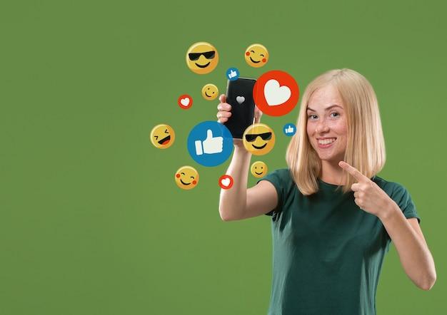 Social media-interacties op mobiele telefoon. digitale internetmarketing, chatten, reageren, leuk vinden. glimlach en pictogrammen boven het smartphonescherm, dat door een jonge vrouw op een groene studioachtergrond wordt vastgehouden.