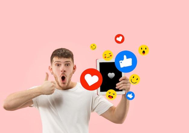 Social media-interacties op mobiele telefoon. digitale internetmarketing, chatten, reageren, leuk vinden. glimlach en pictogrammen boven het tabletscherm, dat door een jonge man op de achtergrond van de koraalstudio wordt vastgehouden.