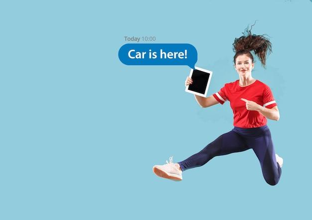 Social media-interacties op mobiele telefoon. digitale internetmarketing, chatten, reageren, leuk vinden. glimlach en pictogrammen boven het tabletscherm, dat door een jonge vrouw op een blauwe studioachtergrond wordt vastgehouden.
