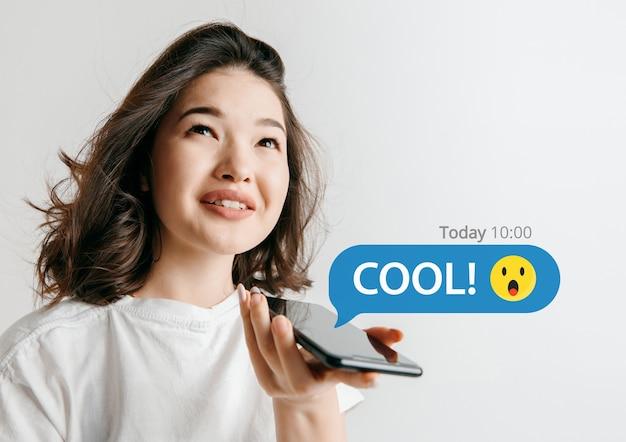 Social media interacties op mobiele telefoon. digitale internetmarketing, chatten, reageren, liken. glimlach en pictogrammen boven het smartphonescherm, dat door een jonge vrouw op een witte studioachtergrond wordt vastgehouden.
