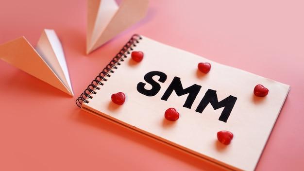 Social media marketingconcept. de inscriptie smm op een roze achtergrond met snoep in de vorm van harten en papieren vliegtuigjes