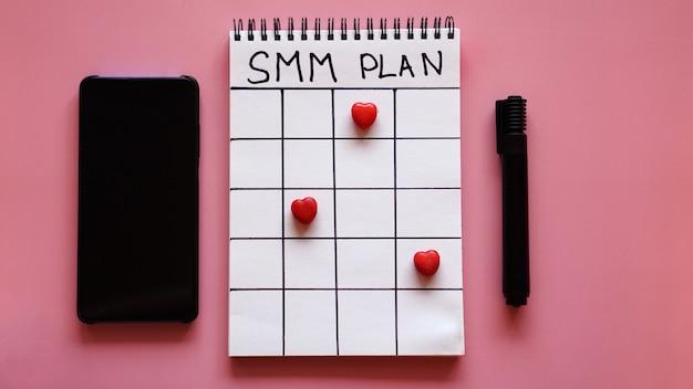 Social media marketingconcept - smm-plan in een notitieboekje op een roze achtergrond met smartphone en snoep in de vorm van harten