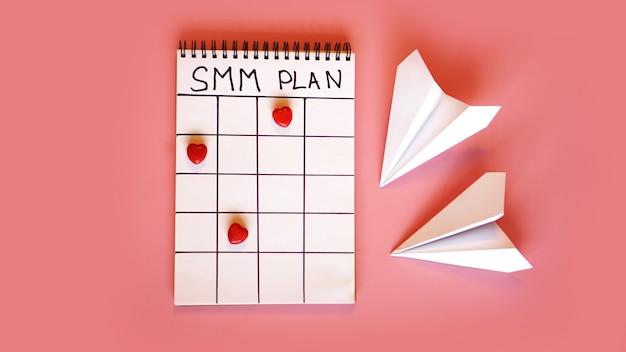 Social media marketingconcept - smm-plan in een notitieboekje op een roze achtergrond met snoep in de vorm van harten en papieren vliegtuigjes