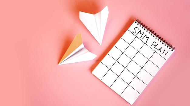 Social media marketingconcept - smm-plan in een notitieboekje op een roze achtergrond