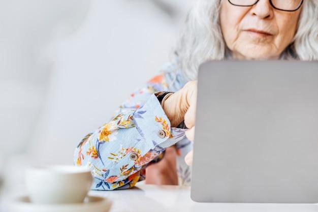 Social media netwerkachtergrond met senior vrouw die op een laptop werkt