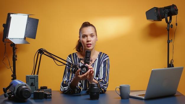 Social media-ster bekijkt twee cameralenzen in haar professionele studio. contentmaker nieuwe media influencer pratende video-fotoapparatuur voor online internetwebshow