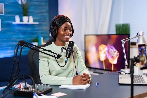 Social media-ster praat voor de camera en neemt een nieuwe aflevering van de show op. sprekend tijdens livestreaming, blogger discussiërend in podcast met koptelefoon op.