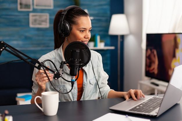 Social media vlogger spreekt met volgers op online podcast met behulp van professionele microfoon. nieuwe mediaster-beïnvloeder die podcastseries opneemt voor publiek