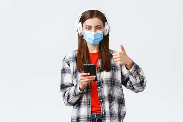 Sociale afstand, levensstijl bij uitbraak van covid-19, coronavirusconcept. vrolijke, goed uitziende vrouw met medisch masker, keur mooi geluid van draadloze koptelefoon goed, duim omhoog, houd telefoon vast.