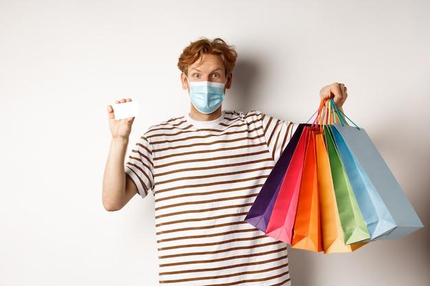 Sociale afstand nemen, coronavirus-concept. jonge man met rood haar, het dragen van gezichtsmasker, boodschappentassen en plastic creditcard, witte achtergrond tonen.
