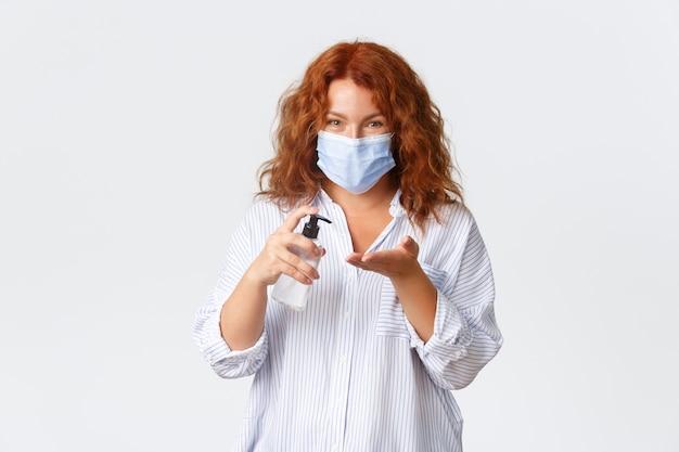 Sociale afstand nemen, maatregelen ter voorkoming van coronavirus en mensenconcept. leuke roodharige dame op middelbare leeftijd die handdesinfecterend middel op handen toepast en medisch masker, veiligheid eerst draagt.