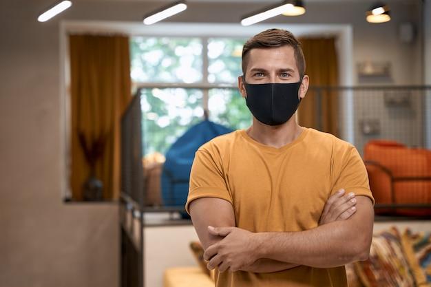 Sociale afstand op het werk portret van jonge zelfverzekerde man mannelijke kantoormedewerker in beschermend gezicht