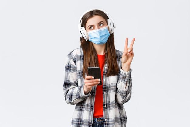 Sociale afstand, vrije tijd en levensstijl bij de uitbraak van covid-19, coronavirusconcept. gelukkig vrolijk dwaas meisje met medisch masker en koptelefoon, laat een vredesteken zien glimlachen, met mobiele telefoon.