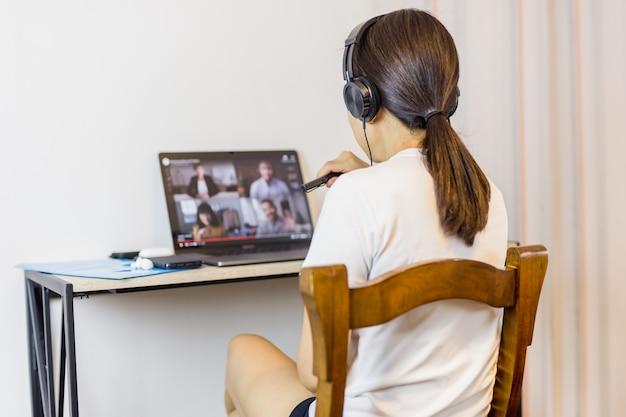 Sociale afstandhoudende vrouw die hoofdtelefoon draagt tijdens groepsvideogesprek met vrienden.