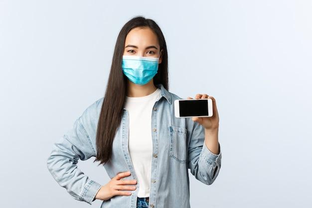 Sociale afstandslevensstijl, covid-19 pandemie en technologieconcept. vrolijke glimlachende aziatische vrouw met medisch masker, die smartphone horizontaal laat zien, promoot app
