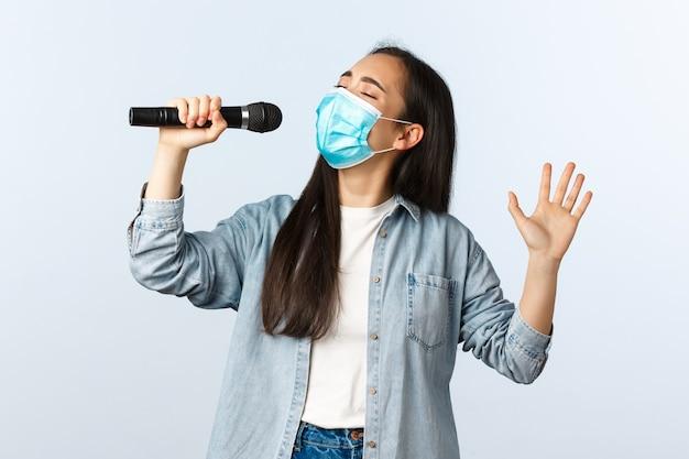Sociale afstandslevensstijl, covid-19 pandemie en zelfisolatie vrijetijdsconcept. zorgeloos ontspannen aziatisch meisje met medisch masker meegesleept in karaoke, zingend in de microfoon.