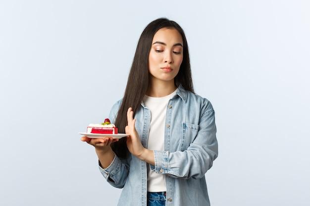 Sociale afstandslevensstijl, covid-19 pandemie, vakantie vieren tijdens het coronavirusconcept. aarzelend arrogant aziatisch meisje dat voor lichaam zorgt, dessert afwijst, onwillig verjaardagstaart eet.