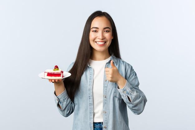 Sociale afstandslevensstijl, covid-19 pandemie, vakantie vieren tijdens het coronavirusconcept. fijne vrolijke aziatische vrouw toont duimen en glimlacht, met een heerlijk cakedessert