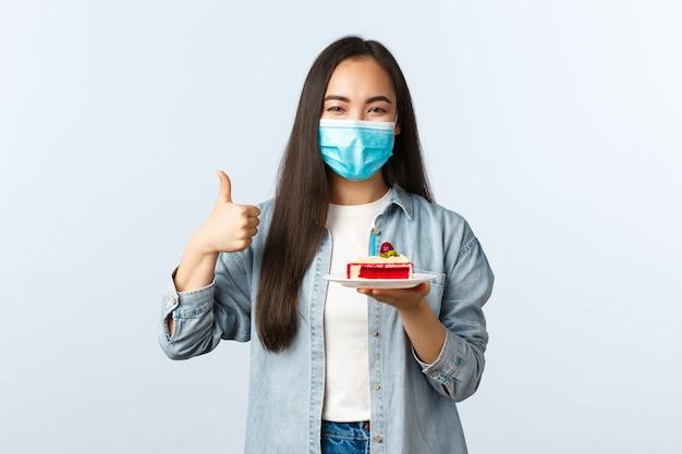 Sociale afstandslevensstijl, covid-19 pandemie, vakantie vieren tijdens het coronavirusconcept. gelukkig lachend aziatisch feestvarken met medisch masker, laat verjaardagstaart zien en duim omhoog tevreden