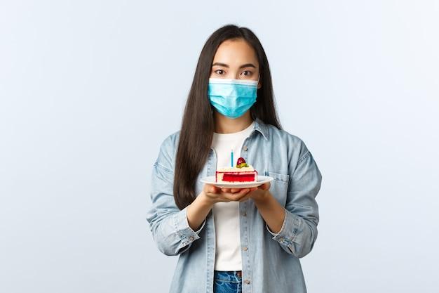 Sociale afstandslevensstijl, covid-19 pandemie, vakantie vieren tijdens het coronavirusconcept. glimlachend dromerig aziatisch meisje in medisch masker met verjaardagstaart, wensen doen op b-day
