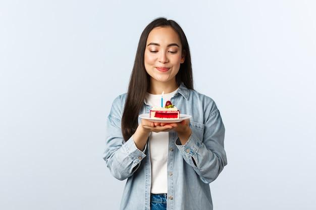 Sociale afstandslevensstijl, covid-19 pandemie, vakantie vieren tijdens het coronavirusconcept. hoopvol dromerig schattig aziatisch meisje glimlachend tevreden over verjaardagstaart, wensen blazende verjaardag kaars.