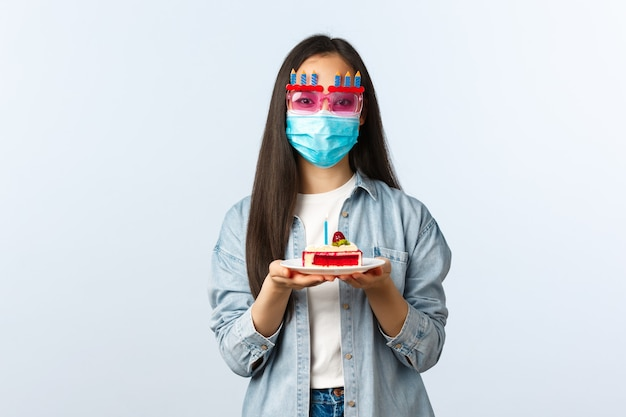 Sociale afstandslevensstijl, covid-19 pandemie, vakantie vieren tijdens het coronavirusconcept. leuke vriendin met medisch masker en feestbril die verjaardagstaart voor verjaardagsmeisjes geeft