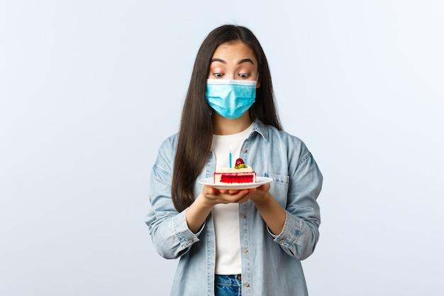Sociale afstandslevensstijl, covid-19 pandemie, vakantie vieren tijdens het coronavirusconcept. opgewonden schattig aziatisch verjaardagsmeisje met medisch masker, verbaasd kijkend naar verjaardagstaart, wensen doen