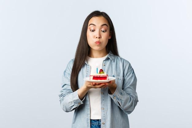 Sociale afstandslevensstijl, covid-19 pandemie, vakantie vieren tijdens het coronavirusconcept. speels schattig en dwaas aziatisch meisje dat pruilt, kaars blaast op verjaardagstaart, wens doet